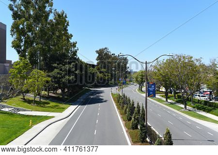 IRVINE, CALIFORNIA - 16 APRIL 2020: Campus Drive looking west seen from Watson Bridge That connects a shopping center with the University of California Irvine, UCI.