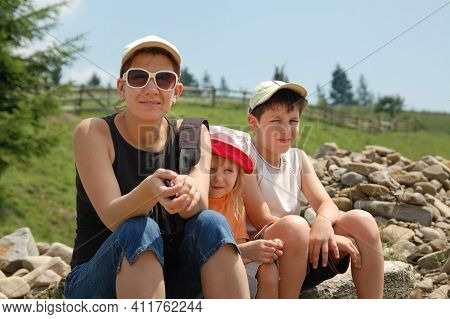 Woman With Children Resting In The Mountains In The Summer. They Sat Down To Rest On The Stones Afte