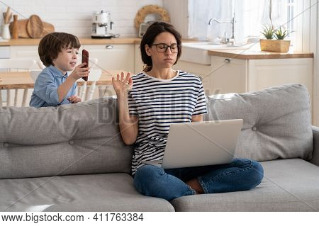 Exhausted Freelancer Mother Sitting On Couch At Home Office During Lockdown, Working On Laptop. Litt