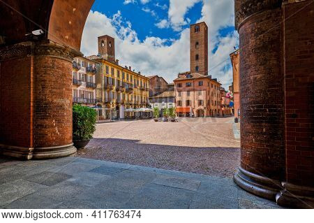 View of cobblestone town square among old houses and medieval towers under beautiful sky in Alba, Piedmont, Northern Italy.