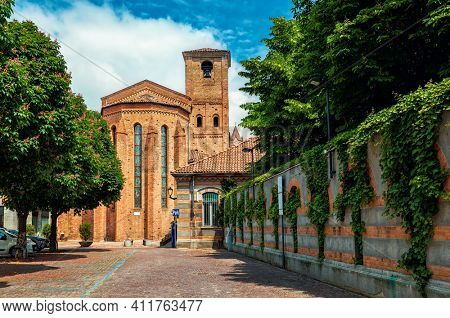 View of narrow cobblestone street and brick catholic church in old town of Alba, Piedmont, Northern Italy.