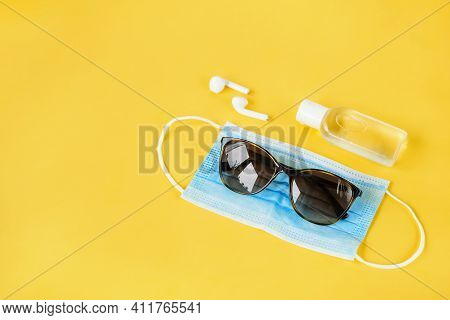 Necessity Kit, Sunglasses, Protective Mask, Sanitiser And Wireless Earpods On Yellow Background. New
