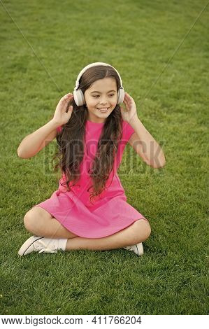 Ambient Sound Headphones. Happy Child Listen To Sound Track Outdoors. Small Girl Enjoy Music Playing