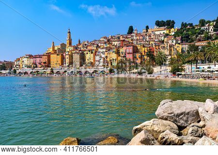 MENTON, FRANCE - AUGUST 03, 2020: People on the beach along the bay as colorful houses on background in Menton - small town in France, famous resort and popular tourist destination on French Riviera.