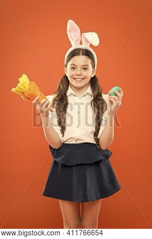 Nibbles A Carrot Like A Hare. Kid In Rabbit Ears Love Eating Carrot. Child Bunny Costume With Carrot