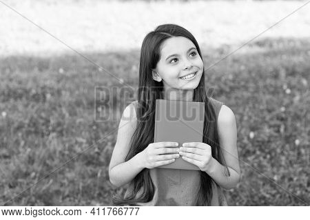 Little Happy Girl Reading Book Outdoors Sunny Day, Daydreamer Concept.
