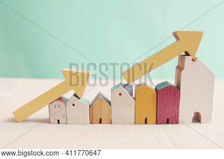 Wooden Houses With Yellow Arrows Up. Housing Boom, Property Market Growing, High Demand For Real Est