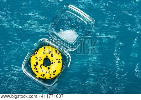 Round Donut With Yellow Glaze In A Plastic Box. Donut With Yellow Glaze On An Old Wooden Table. Donu