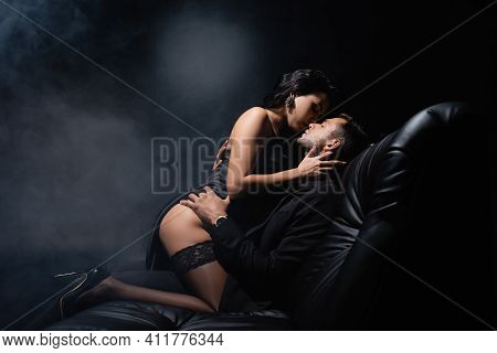 Side View Of Sensual Woman Kissing Boyfriend In Suit On Couch On Black Background With Smoke.