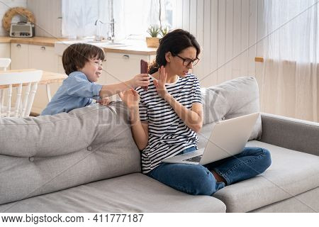 Focused Freelancer Mother Sitting On Couch At Home Office During Lockdown, Working On Laptop. Little