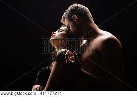 Sexy Man Taking Off Bra From Girlfriend Isolated On Black.