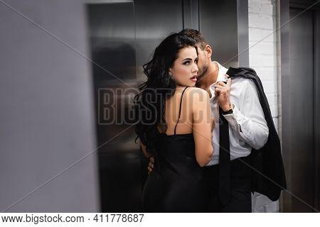 Woman In Dress Looking At Camera Near Passionate Boyfriend In Formal Wear Near Elevator.