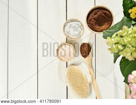 Homemade Exfoliating Scrub Ingredients. Coffee, Pink Salt, Clay Powder And Body Brush On Wooden Tabl