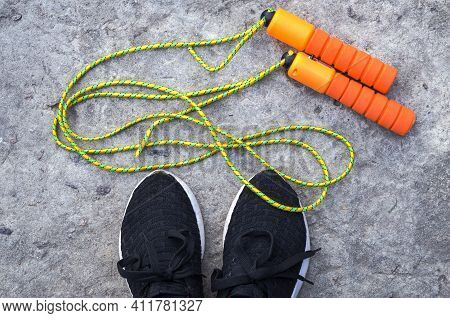 Sports Jump Rope At The Feet Of An Athlete In Sneakers