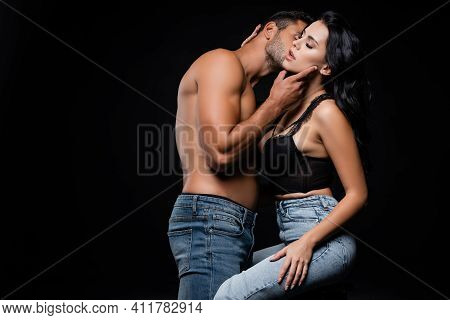 Sexy Man Kissing Passionate Girlfriend Isolated On Black.