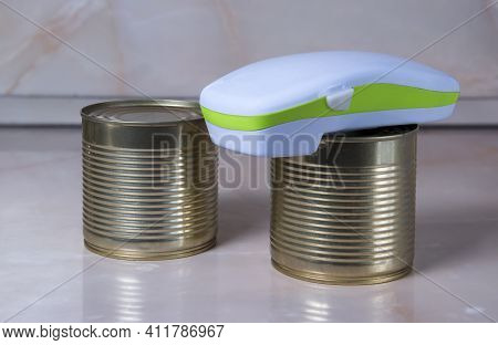 Electric Can Opener And Canned Goods On Kitchen Table
