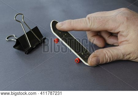 Mini Skate, Binder Clip And Hand On A Gray Background. Male Hand Plays Finger Skateboard. Close-up,
