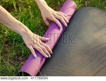 Woman Folding Exercise Mat Before Or After Working Out In The Park. Cropped Image Of Female Putting