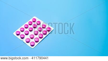 Round Pink Tablets Pills In Blister Pack On Blue Background With Space For Text. Painkiller Medicine