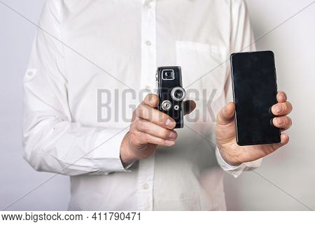 Man Holding Old Retro Camera And New Smartphone Or Phone. Vintage Lens Vs Mobile Phone.