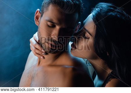 Brunette Woman Whispering To Shirtless Man On Black Background With Smoke.