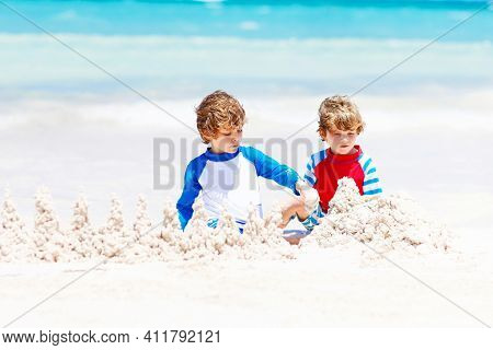 Two Little Kids Boys Having Fun With Building A Sand Castle On Tropical Beach. Happy Children, Sibli