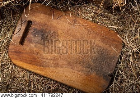 Empty Board For Cutting Food. Board Lying On The Hay. Background From Cutting Boards And Hay. Top.
