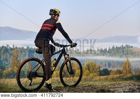 Back View Of Male Cyclist In Cycling Suit Standing With Bike With Coniferous Trees And Hills On Back