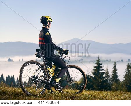 Back View Of Man In Cycling Suit Standing With Bicycle On Grassy Hill And Looking At Beautiful Misty