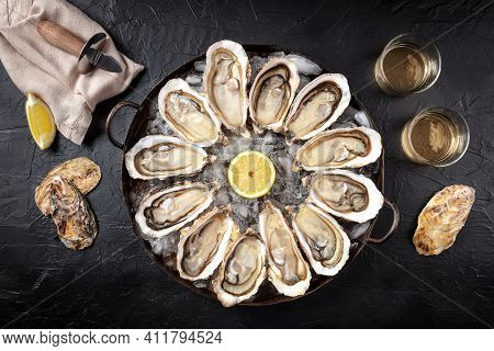 Oyster Dozen, Shot From The Top On A Black Background With Lemon And Wine