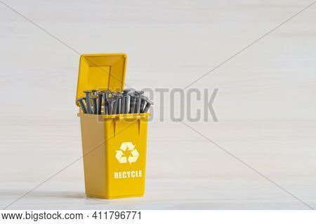 Yellow Plastic Container For Sorting Garbage, With An Open Lid, Nails And An Ecology Icon. Close-up,