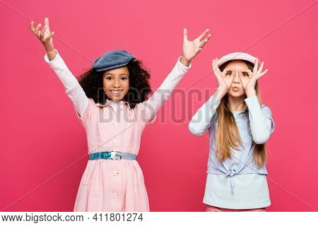 Trendy Girl Imitating Eyeglasses Near Cheerful African American Girl With Raised Hands Isolated On P