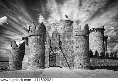 Belmonte Castle In La Mancha Spain. Black And White View With Dramatic Sky With Clouds And Long Phot