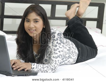 A Pretty Lady Relaxing At Home On The Laptop