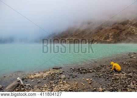 Tourist Trying To Take A Photograph Of The Mystery Gokyo Lakes Covered With Fog In Gokyo Village, Ne