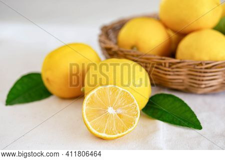 Group Of Whole And Cut Organic Lemon In Wood Basket On White Background. Fresh Lemon Have High Vitam