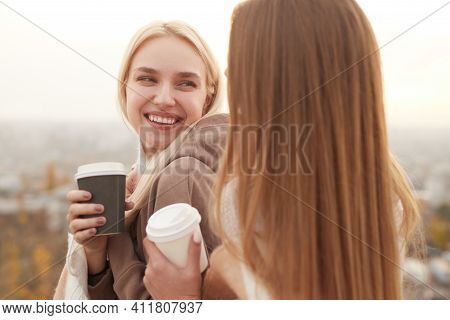 Content Female Best Friends With Takeaway Coffee In Paper Cups Cuddling At Sunset In City And Lookin