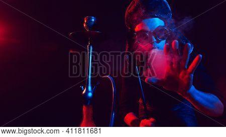 Male Smoker With A Beard Smokes A Hookah And Blows Out A Cloud Of Smoke