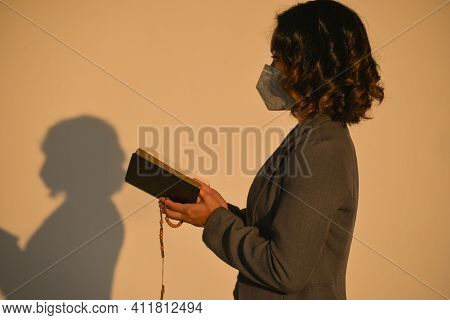 Pray And Bible Concept. Asian Female Were Medical Mask Praying, Hope For Peace And Free From Disease