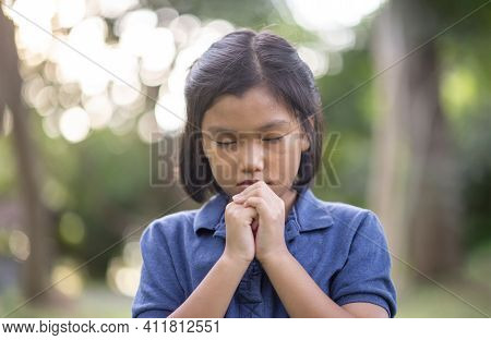 Prayer Concept. Asian Child Praying, Hope For Peace And Free From Coronavirus, Hand In Hand Together