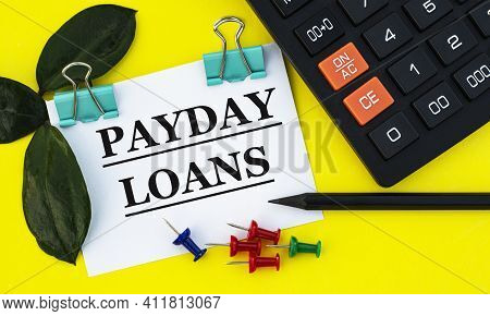 Payday - Words On White Sheet With Clips On Yellow Background With Calculator, Buttons, Pencil And G