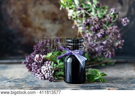Oregano Essential Oil In Glass Bottle On Wooden Background. Copy Space