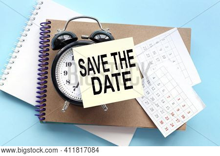 Save The Date. Text On The Sticker Attached To The Alarm Clock. Alarm Clock On Notepad On Blue Backg