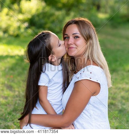 Little girl hugs and kiss her mother in summer forest nature outdoor. Portrait of mom and daughter. Family walks barefooted in park. Trust, kindness, maternity, parenthood, confidence, mother's love