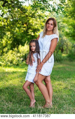 Outdoor portrait of mom and daughter wearing white clothes against summer greenery. Family walks barefooted in park. Trust, kindness, maternity, parenthood, confidence, mother's love concept.