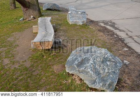 A Bench In A Park Made Of One Half Of A Massive Trunk. It Is A Heavy Wooden Product With A Natural,