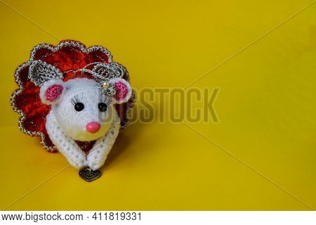Knitted White Rat In A Red Skirt On A Yellow Background. The Rat Holds A Small Copper Heart In His H