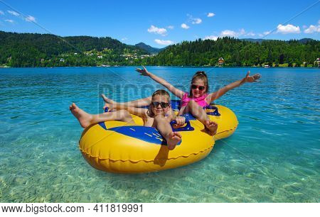 Boy and girl on inflatable float in lake. Little children floating in yellow raft on surface water.  Bled. Slovenia, Europe.