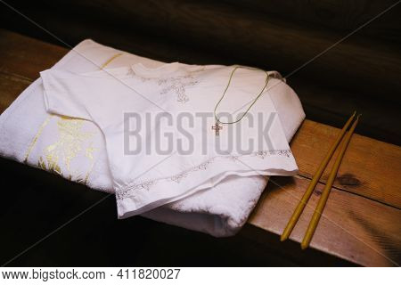 White Baptismal Shirt With A Cross In The Temple. Cooking At The Traditional Rite Of Baptism