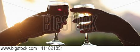 Male And Female Hands Are Holding Glass Of Red And White Wine Against Sunset Background. Romantic Da